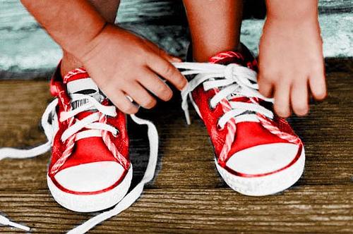 Child tying shoelace